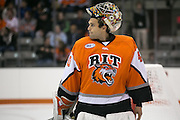 RIT's Jordan Ruby lifts his mask during a stoppage in play during a game against Brock University at the Gene Polisseni Center on Saturday, October 4, 2014.