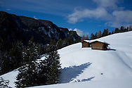 Wooden barns on a snowy slope at the Alpe di Siusi ski resort near Ortisei in The Dolomite Mountains, South Tyrol, Italy