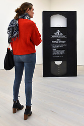"© Licensed to London News Pictures. 27/09/2018. LONDON, UK. A visitor views ""VHS"", 2005, by David Herbert.  Preview of ""Black Mirror"", a major new exhibition featuring the work of 26 contemporary artists, at the Saatchi Gallery.  The show explores art's role in social satire and how political uncertainty has influenced art of recent years and runs 28 September to 13 January 2019.   Photo credit: Stephen Chung/LNP"