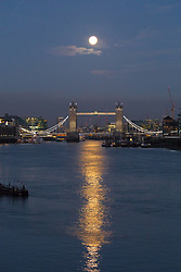 © Licensed to London News Pictures. 04/11/2017. London, UK. The December supermoon is seen shortly before sunrise behind Tower Bridge, reflecting on the River Thames this morning. Photo credit: Vickie Flores/LNP