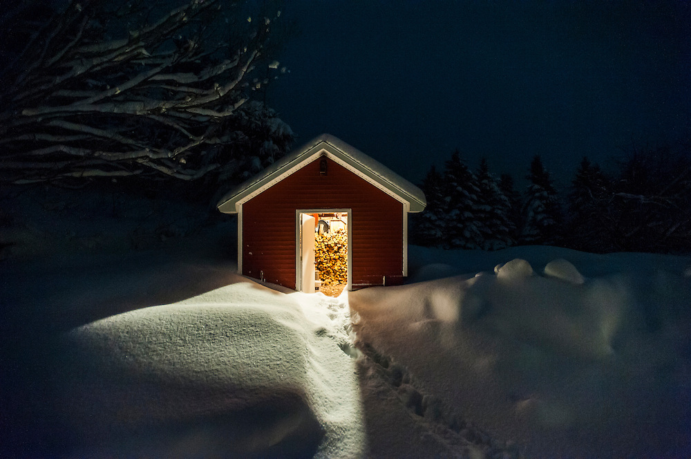 A light shines onto big snowbanks from within a woodshed on a farm in winter in Northern Michigan.