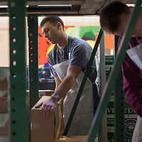 Bodee Hancock, left, and Caleb Thompson, volunteers from the Church of Jesus Christ of Latter-day Saints, work in the warehouse of the Community Pantry in Gallup Wednesday.