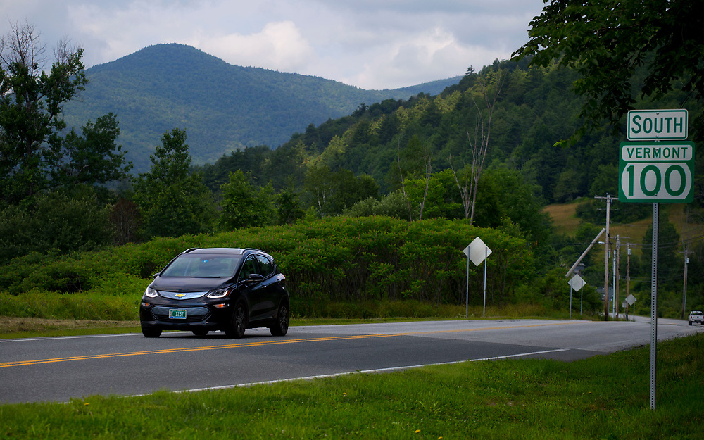 Kevin Jones, of Chittenden, Vt., travels on Route 100 in Stockbridge, Vt., near the Green Mountain National Forest on July 12, 2017. After owning two gas-electric hybrids, Jones decided to lease a Chevy Bolt electric car for his 80-mile roundtrip commute. Because its brakes regenerate the battery power, Jones said the downhill travel in the mountains compensates for its uphill climb. (Photo by Geoff Hansen)