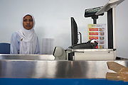 Young cashier wearing the hejab awaits customers at the state-run MIFCO exporting 100% Maldivian seafoods to Europe and Asia .