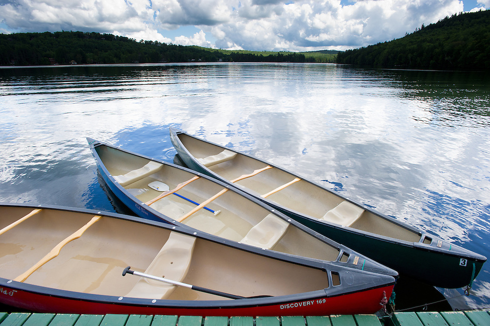 Canoes at dock with blue sky reflecting in water in Bryant Pond, Maine