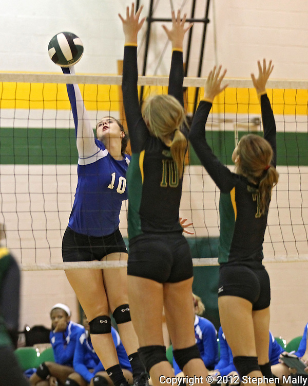 Washington's Danielle Franklin (10) puts up a kill shot past Hempstead's Haley Van Cleave (10) and Rachel Cummer (7) during the MVC Volleyball Tournament Championship game between the Hempstead Mustangs and the Washington Warriors at Kennedy High School in Cedar Rapids on Saturday October 13, 2012. Hempstead defeated Washington 25-21 25-19.