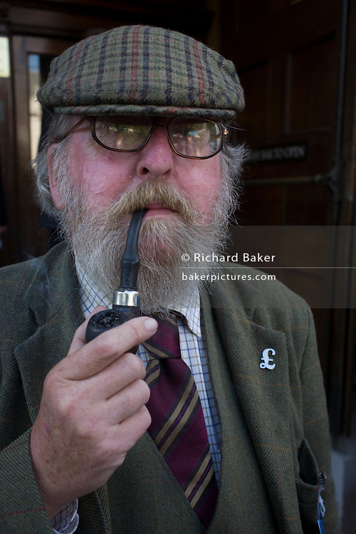 An elderly UKIP (UK Independence Party) member sucks on a pipe outside the party conference in Westminster, central London.
