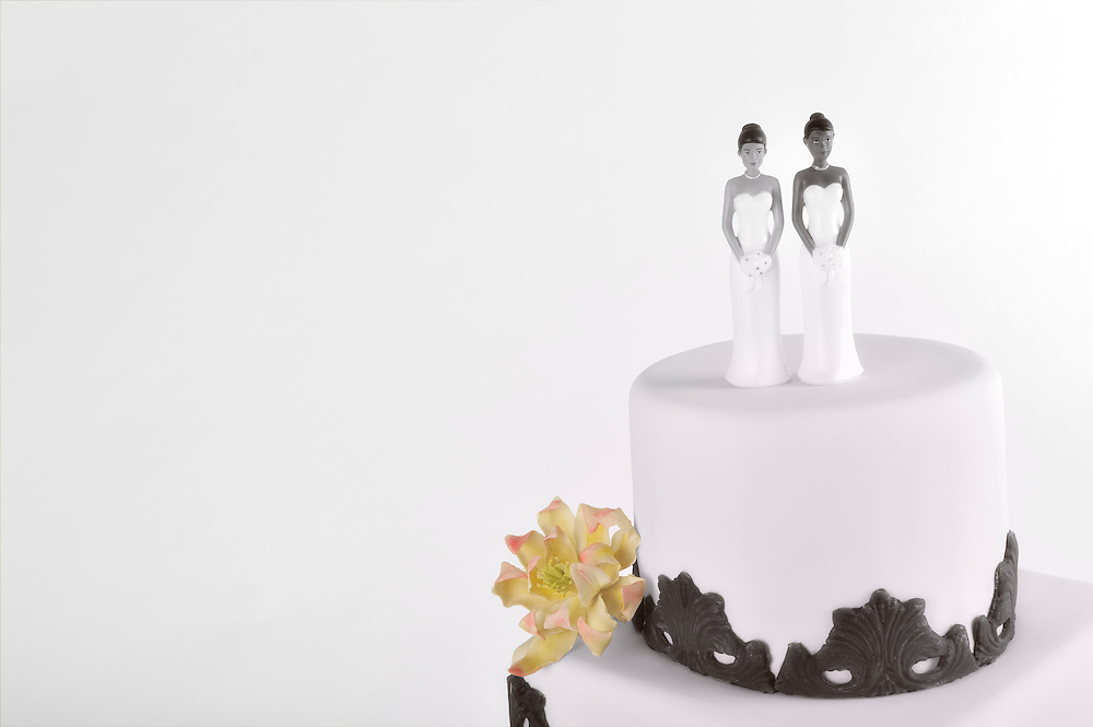 In support of gay marriage: Wedding Cake with two women lesbian couple, with copy space. Close-up view of top of tiered wedding cake with female figurines. Dreamy romantic soft-focus. Marriage equality.