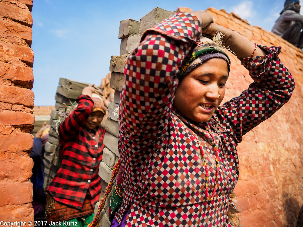 03 MARCH 2017 - BAGMATI, NEPAL: Women carry wet, unbaked, bricks into a kiln at a brick factory in Bagmati, near Bhaktapur. There are almost 50 brick factories in the valley near Bagmati. The brick makers are very busy making bricks for the reconstruction of Kathmandu, Bhaktapur and other cities in the Kathmandu valley that were badly damaged by the 2015 Nepal Earthquake. The brick factories have been in the Bagmati area for centuries because the local clay is a popular raw material for the bricks. Most of the workers in the brick factories are migrant workers from southern Nepal.       PHOTO BY JACK KURTZ