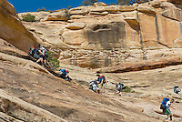 Group of teenaged backpackers making their way down a steep slickrock section of Bullet Canyon, Grand Gulch Primitive Area, Cedar Mesa Utah Bears Ears National Monument
