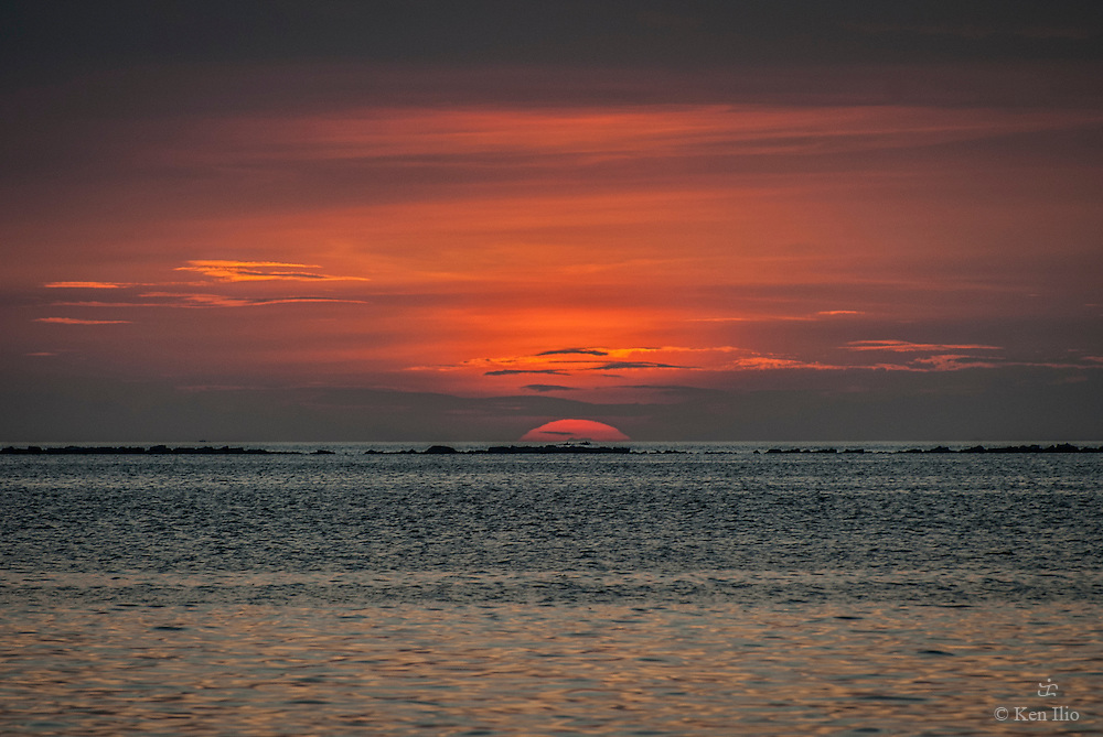 Sun disappearing below the horizon in Manila Bay, Manila, Philippines