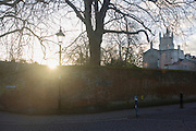 As a wintry sun sets early over the walls of Winchester College, is the corner of College Street and College Walk. .Winchester College is an independent school for boys in the British public school tradition, situated in Winchester, Hampshire, England. It has existed in its present location for over 600 years and claims the longest unbroken history of any school in England. It is the oldest of the original nine English public schools defined by the Public Schools Act 1868