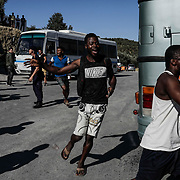 Congolese asylum seekers race toward buses that will take them to the Mytilene ferry port which will take them to Athens from Moria camp. Authorities planned to move 200+ asylum seekers a day after a fatal fire and clashes with police took place at the camp on Lesvos Island in Greece on Monday, September 30, 2019.