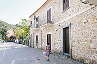 ACCIAROLI, ITALY - 14 SEPTEMBER 2018: An elderly woman walks back home after buying groceries in Acciaroli, a small fishing village in the municipality of Pollica, Italy, on September 14th 2018.<br /> <br /> To understand how people can live longer throughout the world, researchers at University of California, San Diego School of Medicine have teamed up with colleagues at University of Rome La Sapienza to study a group of 300 citizens, all over 100 years old, living in Acciaroli (Pollica), a remote Italian village nestled between the ocean and mountains in Cilento, southern Italy.<br /> <br /> About 1-in-60 of the area's inhabitants are older than 90, according to the researchers. Such a concentration rivals that of other so-called blue zones, like Sardinia and Okinawa, which have unusually large percentages of very old people. In the 2010 census, about 1-in-163 Americans were 90 or older.