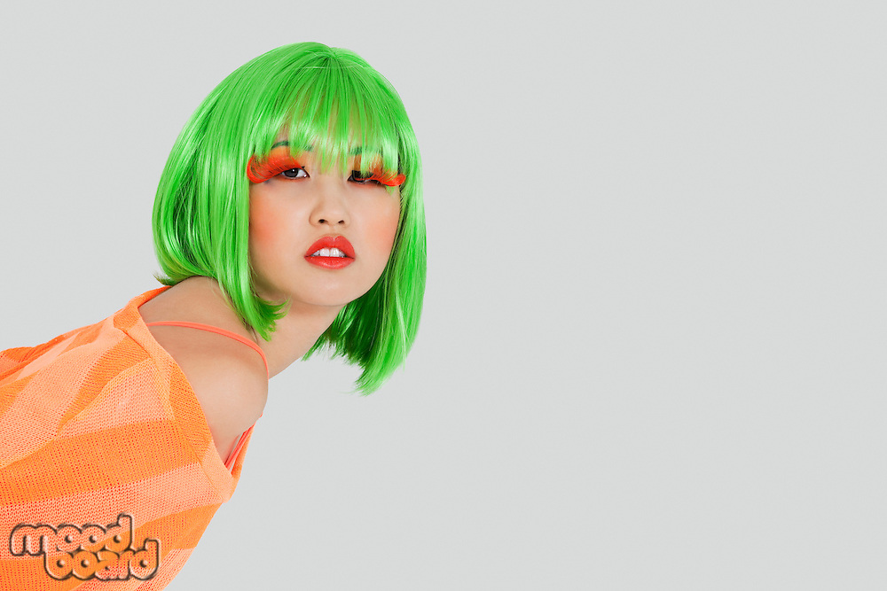 Portrait of young woman wearing green wig over gray background