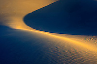 A simple shape emerges from the interaction of shadow and light, Death Valley National Park, USA.