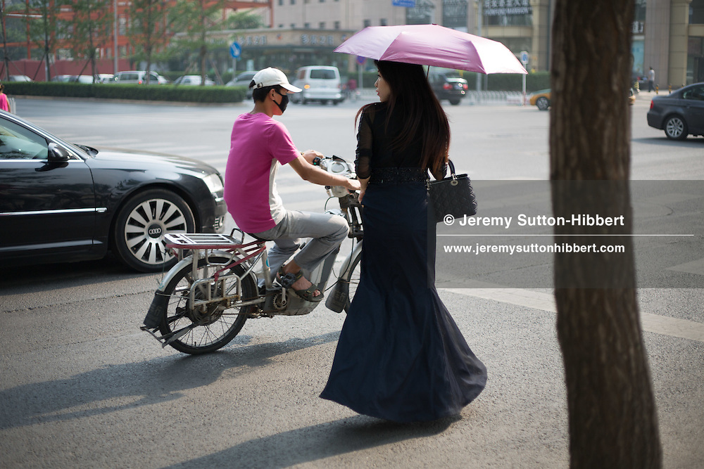 Woman wearing evening wear dress, with mobile telephone, in a shopping mall, in Beijing, China, Thursday 7th June 2012.