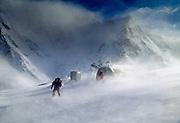 Skiers leave Barron Saddle hut in blowing snow, Mueller glacier, Aoraki Mount Cook National Park, New Zealand.