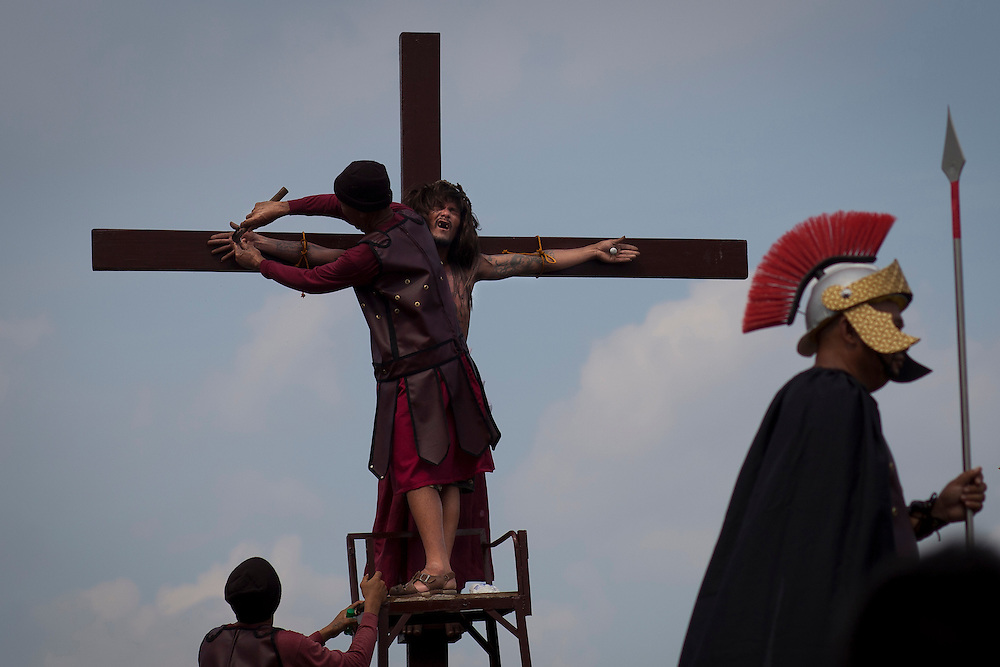 Volunteers dressed as Roman Centurions, drive nails through the palms of an unidentified Catholic devotee in a reenactment of the crucifixion of Jesus Christ on Good Friday at San Pedro Cutud, Pampanga province, north of Manila, Philippines Friday, April 6, 2012. More than two dozen Catholic devotees have themselves nailed on the cross on Good Friday, a practice rejected by the Catholic Church but has become a tourist attraction.
