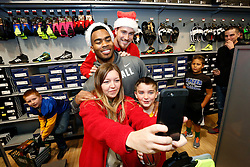 "Kansas City Chiefs players, Travis Kelce, right, and Charcandrick West, left, pose for photos as they accompany members of the Football and Cheerleading Club of Johnson County as they shop for items on their ""wish list"" at the ""Sports Matter"" Holiday Shopping event hosted by DICK'S Sporting Goods on Thursday, Dec. 17, 2015, in Leawood, KS. (Colin E. Braley/AP Images for Dick's Sporting Goods)"