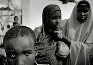 A blinded boy and his severely traumatized sister at a local feeding center in the city - many disabled and traumatized IDP´s turn up every day in order get a minimum of aid and food due to the lack of help for disabled - Due to the lack of security only a few organisation are able to help the many refugees.<br /> Mogadishu;SomaliaThe Horn of Africa is facing a severe crisis due to the convergent effects of the worst droughts in decades, and the persistent effects of armed conflict in Somalia, which has combined to trigger one of the sharpest refugee outflows in a decade to Kenya and Ethiopia. Over ten million people are at high risk including 2.85 million persons in Somalia, 3.2 million in Ethiopia and 3.5 million in Kenya.–– Despite access and security limitations, UNICEF is working with local partners in Somalia to bring much-needed relief to over 200,000 people newly displaced by the recent upsurge in conflict in the capital, Mogadishu. - For hundreds of thousands of displaced Somali children, daily life is a mixture of fear and insecurity. Communities break apart, as one by one families leave their villages to flee ongoing conflict. If they survive the journey to Mogadishu, life is not much easier, as they are faced with the daily challenge of finding food and shelter.<br /> For children, this experience can be traumatizing. Having fled their homes in search of safety, they find themselves in overcrowded camps, away from all they know.<br /> While most children arrive in the displaced camps with their families, some are tragically separated from their parents and are either left to fend for themselves or forced to rely on already overburdened community members. Each Child Friendly Space has facilitators from UNICEF's NGO partners who work with the children. Several of the partners also have social workers to help identify and refer children in need of care and protection to the appropriate services. Somalia.