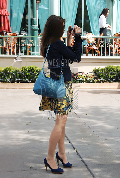 Young woman tourist with blue handbag taking a video on a city street