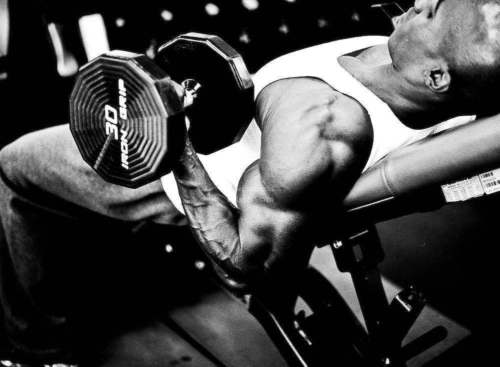 Anu McKnight, amateur bodybuilder, doing incline bench bicep curls with dumb bells.