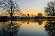 UNITED KINGDOM, London: 18 January 2017 The reflection of cyclists can be seen in a small lake in Richmond Park during sunrise this morning. Temperatures dropped to -4C in certain parts of the capital last night causing wide spread frost. Rick Findler / Story Picture Agency
