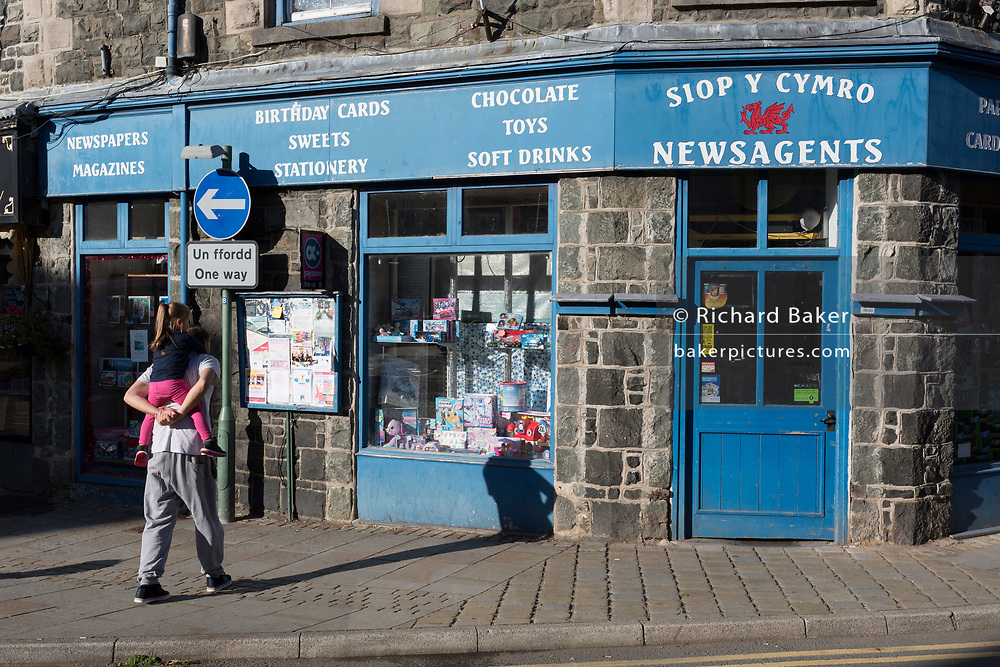 A man and child outside the newsagents and gift shop on Eldon Square, on 12th September 2018, in Dolgellau, Gwynedd, Wales.