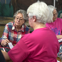 Utha Russell, left, and Lynn Olinger, right, organize the quilts to be hung in the Grants Community Center Thursday for the show this weekend. The Mount Taylor Quilt Guild received 75 quilts to be entered for judging and a silent auction.