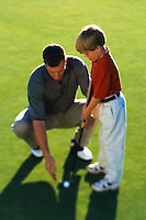 Father Teaching Son to Golf --- Image by © Jim Cummins/CORBIS