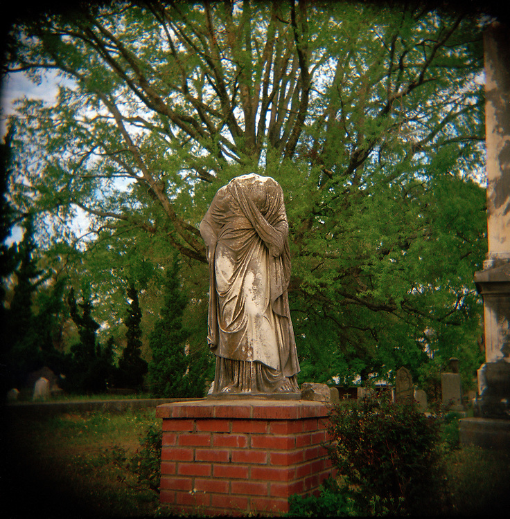 Jackson, Mississippi- A headless statue arises from the vegetation at the Greenwood Cemetery where writer Eudora Welty is buried.