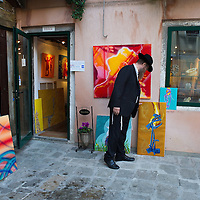 VENICE, ITALY - NOVEMBER 15: Painter David de Guglielmi arranges some of the paints on display in front of his atelier at the Venice Ghetto on November 15, 2011 in Venice, Italy. Established in 1516 the Ghetto of Venice was the area were Jews were compelled to live during the Venetian Republic. The English term 'ghetto' is derived from the Venetian term for 'slag' and refers to the refuse left the foundry that was located on the same island. In present times the ghetto is a multi-ethnical area area seen as the cultural heart of the city, but with five synagogues remains the centre of the of Jewish community.