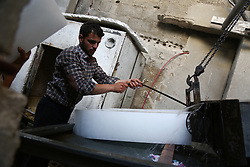 June 17, 2017 - Damascus, Syria - The worker holds the ice cube after finishing the manufacturing  in Douma of Damascus, Syria, on 19 June 2017. (Credit Image: © Samer Bouidani/NurPhoto via ZUMA Press)