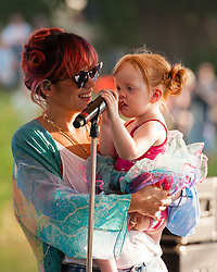 © Licensed to London News Pictures. 18/07/2014. Southwold, UK.   Lily Allen with her daughter at her recording of a special live performance for the Andrew Marr Show from The Latitude Festival on a riverside stage.   Lily Allen replaced Two Door Cinema Club as tonight's headline act - this was announced earlier this week as a result of Two Door Cinema Club's frontman Alex Trimble's ill health.  It was reported Trimble collapsed at an american airport.  Latitude is British annual music festival.  Photo credit : Richard Isaac/LNP