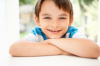 Young boy leaning into window of house portrait close up