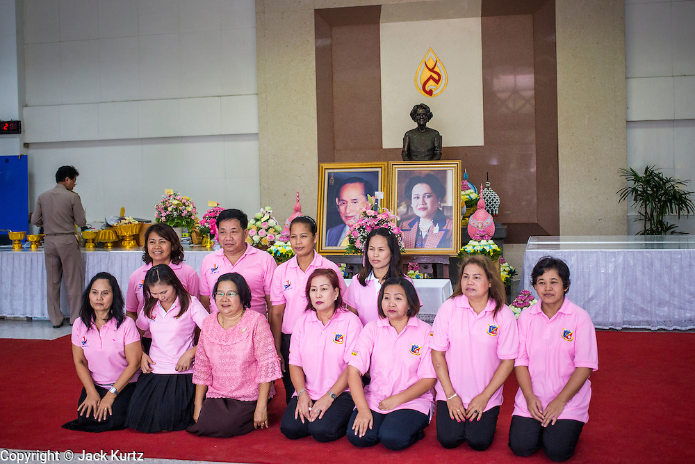 26 NOVEMBER 2012 - BANGKOK, THAILAND:  Thai civil servants pose in front of picture of the King and Queen of Thailand after paying their respects to the monarchy at Siriraj Hospital in Bangkok. They were wearing pink because it's viewed as a fortuitous color that could bring the King better health. Siriraj was the first hospital in Thailand and was founded by King Chulalongkorn in 1888. It is named after the king's 18-month old son, Prince Siriraj Kakuttaphan, who had died from dysentery a year before the opening of the hospital. It's reported to one of the best hospitals in Thailand and has been home to Bhumibol Adulyadej, the King of Thailand, since 2009, when he was hospitalized to treat several ailments. Since his hospitalization tens of thousands of people have come to pay respects and offer get well wishes. The King's 85th birthday is on Dec 5 and crowds at the hospital are growing as his birthday approaches. The King is much revered throughout Thailand and is seen as unifying force in the politically fractured country.       PHOTO BY JACK KURTZ
