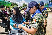 "25 OCTOBER 2012 - TAK BAI, NARATHIWAT, THAILAND: Members of the Thai Army check the ID's of people entering Tak Bai, Thailand. The ""Tak Bai Incident"" took place on Oct. 25 in Tak Bai, Narathiwat, Thailand during the Muslim insurgency in southern Thailand. On that day, a crowd gathered to protest the arrest of local residents. Police made hundreds of arrests during the protest and transported the arrested to Pattani, about two hours away, in another province. They were transported in locked trucks and more than 80 people suffocated en route. This enraged local Muslims and shocked people across Thailand. No one in the Thai army accepted responsibility for the deaths and no one was ever charged. In the past, the anniversary of the incident was marked by protests and bombings. This year it was quiet. More than 5,000 people have been killed and over 9,000 hurt in more than 11,000 incidents, or about 3.5 a day, in Thailand's three southernmost provinces and four districts of Songkhla since the insurgent violence erupted in January 2004, according to Deep South Watch, an independent research organization that monitors violence in Thailand's deep south region that borders Malaysia.   PHOTO BY JACK KURTZ"