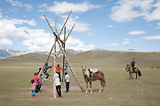 Children play on a swing at a Kyrgyz horse games festival. Bosogo jailoo, Naryn province, Kyrgyzstan.
