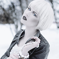 A young adult with short platinum blond hair and black lipstick wears a leather coat in the snow, looking like a dark fantasy character