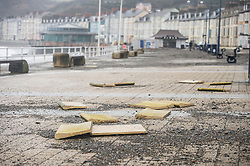 © London News Pictures. 08/02/2016. Aberystwyth, UK.  Damage caused by the impact of Storm Imogen is seen clearly in Aberystwyth after the high tides have subsided. Debris from the beach and ripped up pavement slabs litter the promenade and seafront road. Photo credit: Keith Morris/LNP