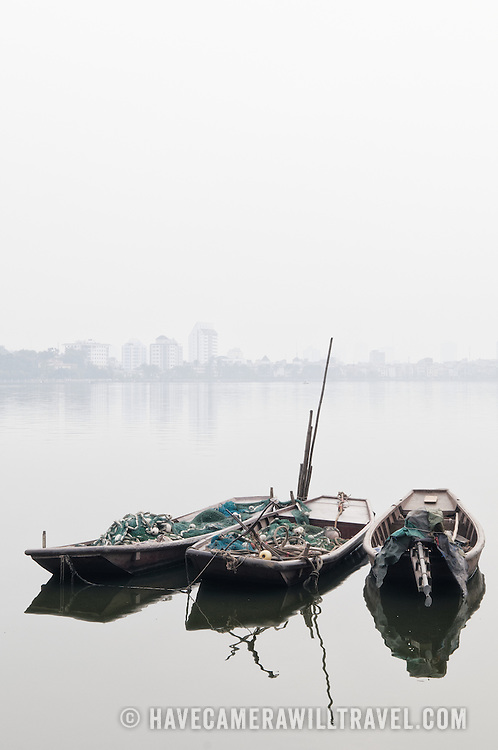 Three wooden sampans moored on West Lake (Ho Tay) in Hanoi, Vietnam. The heavy haze mostly obscures the far shore. Vertical shot with copyspace.