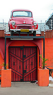 Bright red, old model car with license plates saying Havanna sits above the entrance to a restaurant in Gaborone, Botswana. Gaborone is the capital city of Botswana, and is considered one of the fastest growing cities in Africa.