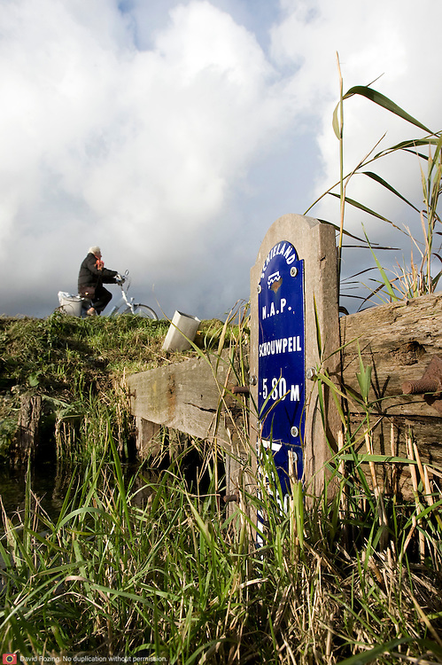 Nederland Zevenhuizen 12 november 2008 20081112 Foto: David Rozing ..Serie Zuidplaspolder, schouwpeil NAP bordje in watergang, meer dan 6 meter onder NAP..De Zuidplaspolder is de laagste plek in Nederland en Europa, het laagste punt in de polder meet 6,76 meter onder NAP. Omdat het gebied zo laaggelegen is zijn  plannen voor deze polder omstreden/ is er een felle discussie over.  .De Zuidplaspolder is in de Nota Ruimte aangewezen als één van de grote ontwikkelingslocaties in Nederland.  Er moeten 15.000 tot 30.000 nieuwe woningen komen, 150 tot 250 ha bedrijventerreinen, mogelijk 200 ha extra glastuinbouw en waterberging. Om deze verstedelijking mogelijk te maken wordt de grens van het Groene Hart aangepast. Duurzaamheid is een belangrijk onderdeel bij de planning en uitvoering..Het gebied is aangewezen als studielocatie voor stadsuitbreiding. Tegenstanders geven aan dat gezien de diepte van de polder waterproblematiek zich onafwendbaar zal gaan voordoen. Voorstanders geven aan dat met aanpassingen in het watersysteem en goede planning zoals wonen, werken, recreëren gepland op plekken waar dat gezien het water en de bodem het meest gunstig het een veilige omgeving zal zijn. ..Foto: David Rozing