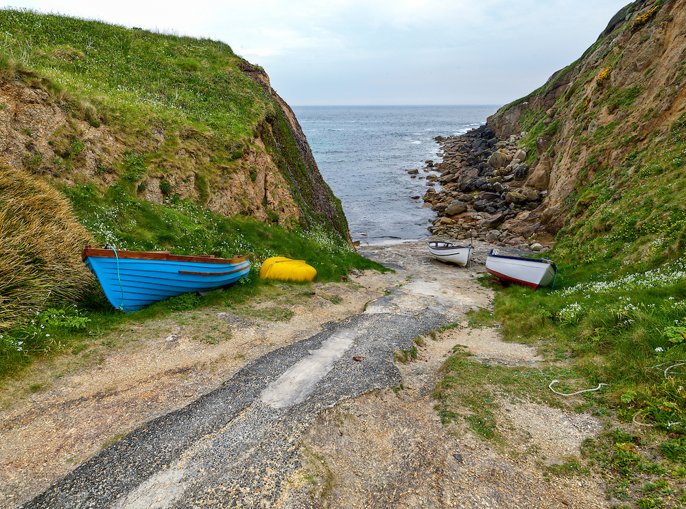 Small boats alongside launching ramp on the Cornwall coastline in England