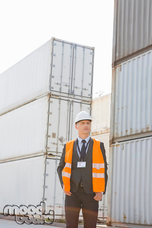 Middle-aged man standing against cargo containers in shipping yard