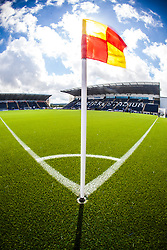 An upright image of the corner flag in sunlight, with the main stand behind. The Falkirk Stadium, with the new pitch work for the Scottish Championship game v Morton. The woven GreenFields MX synthetic turf and the surface has been specifically designed for football with 50mm tufts compared with the longer 65mm which has been used for mixed football and rugby uses.  It is fully FFA two star compliant and conforms to rules laid out by the SPL and SFL.<br /> &copy;Michael Schofield.
