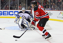 Jan 17; Newark, NJ, USA; New Jersey Devils center Steven Zalewski (10) skates with the puck by Winnipeg Jets goalie Chris Mason (50) during the second period at the Prudential Center.
