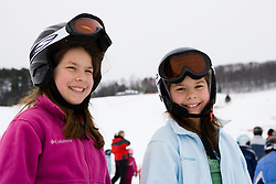 Twin girls (age 11) wait for the tow rope at the Quechee Ski Hill in Quechee, Vermont. Model Release.