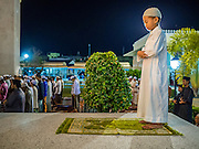 18 JUNE 2015 - PATTANI, PATTANI, THAILAND:  A boy prays near the front door of Pattani Central Mosque on the first day of Ramadan. Thousands of people come to Pattani Central Mosque in Pattani, Thailand, to mark the first night of Ramadan. Ramadan is the ninth month of the Islamic calendar, and is observed by Muslims worldwide as a month of fasting to commemorate the first revelation of the Quran to Muhammad according to Islamic belief. This annual observance is regarded as one of the Five Pillars of Islam. Islam is the second largest religion in Thailand. Pattani, along with Narathiwat and Yala provinces, all on the Malaysian border, have a Muslim majority.    PHOTO BY JACK KURTZ